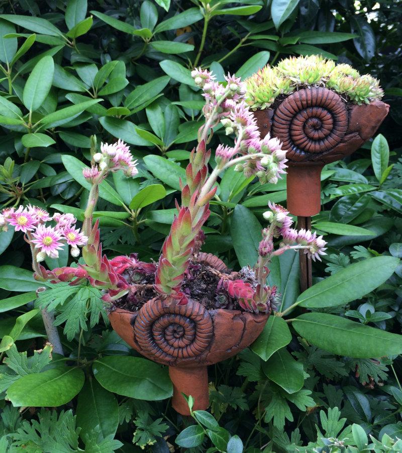 Gartenstecker aus roter Keramik vor Rhododendron